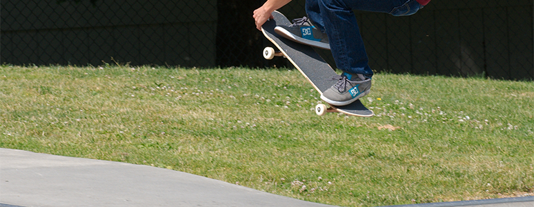 photograph of feet jumping off a ramp on a skateboard with grass in background