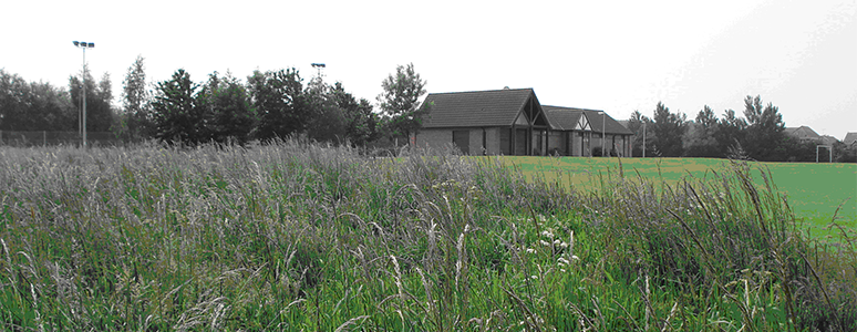 Image of chellaston community building in distance with grass and long grass in foreground