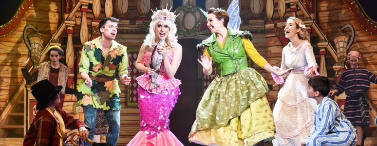 A group scene from Peter Pan with Peter dressed in green, a mermaid dressed in pink, Tinker Bell the fairy dressed in green, and Wendy in a victorian style nightdress